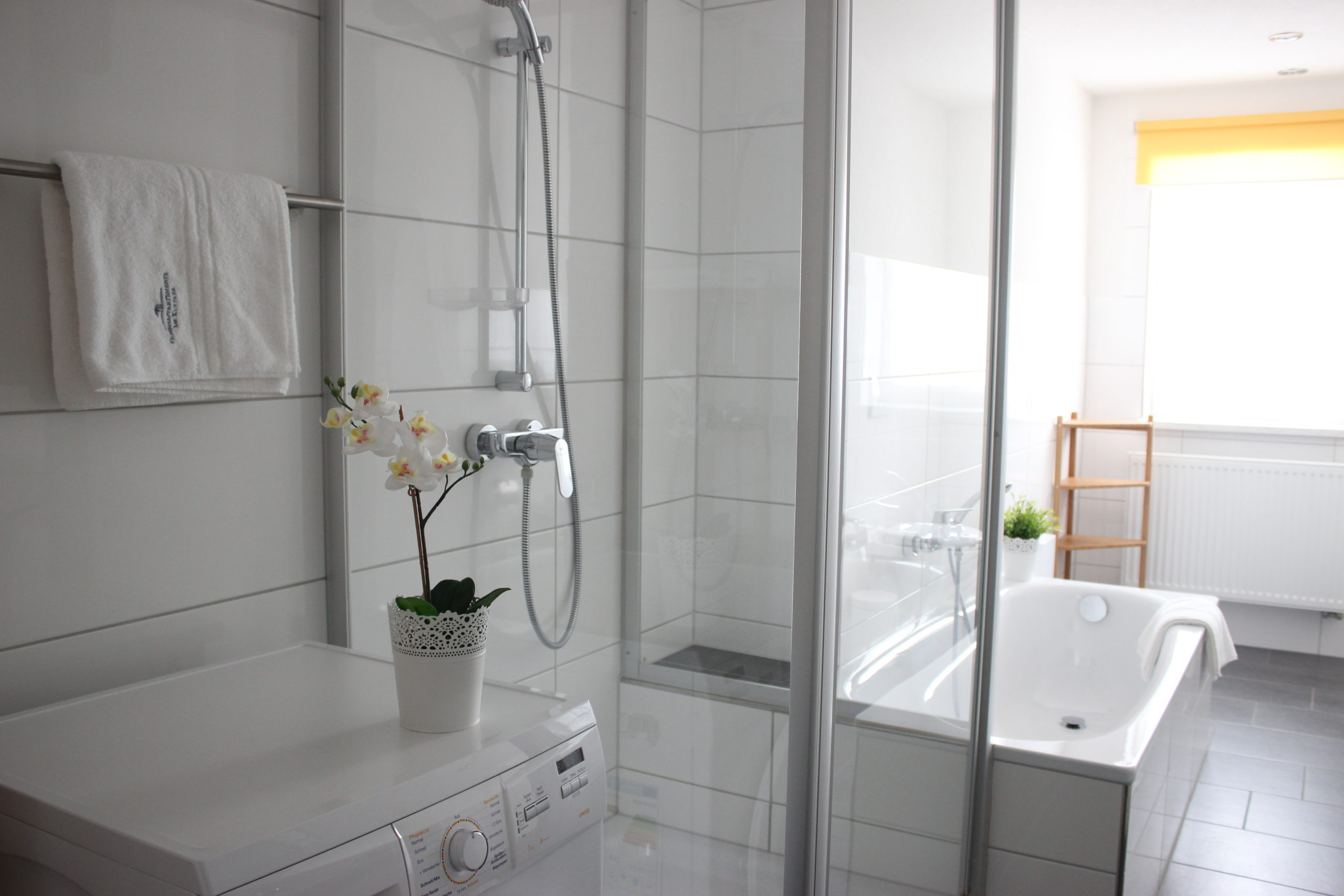 Badezimmer mit Waschmaschine, Dusche & Badewanne